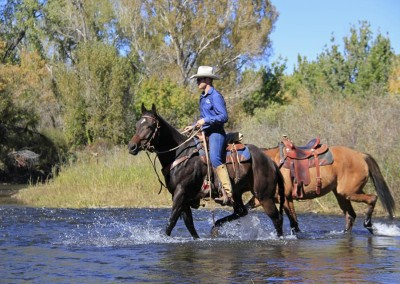 Cody crossing water on Louie, ponying Bell